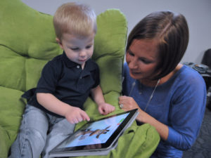 child with mother interacting with online reading games
